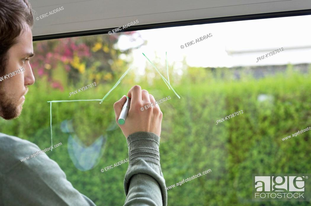 Stock Photo: Man drawing an architecture design on the glass of window.