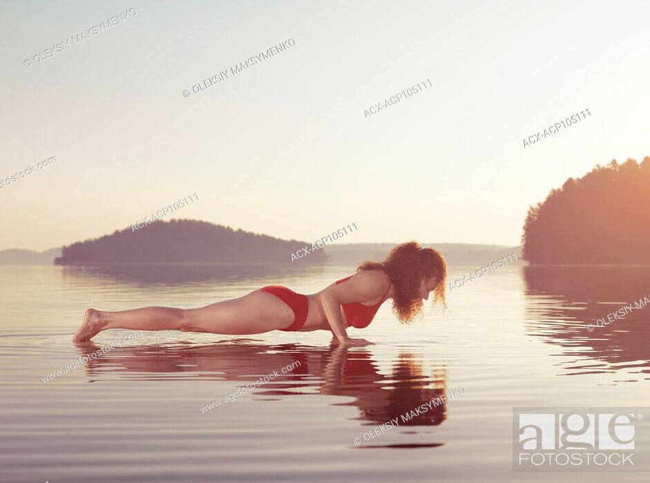 Stock Photo: Young woman practicing Hatha yoga on a floating platform in water on the lake during misty sunrise in the morning. Yoga or pilates Plank posture, Kumbhakasana.