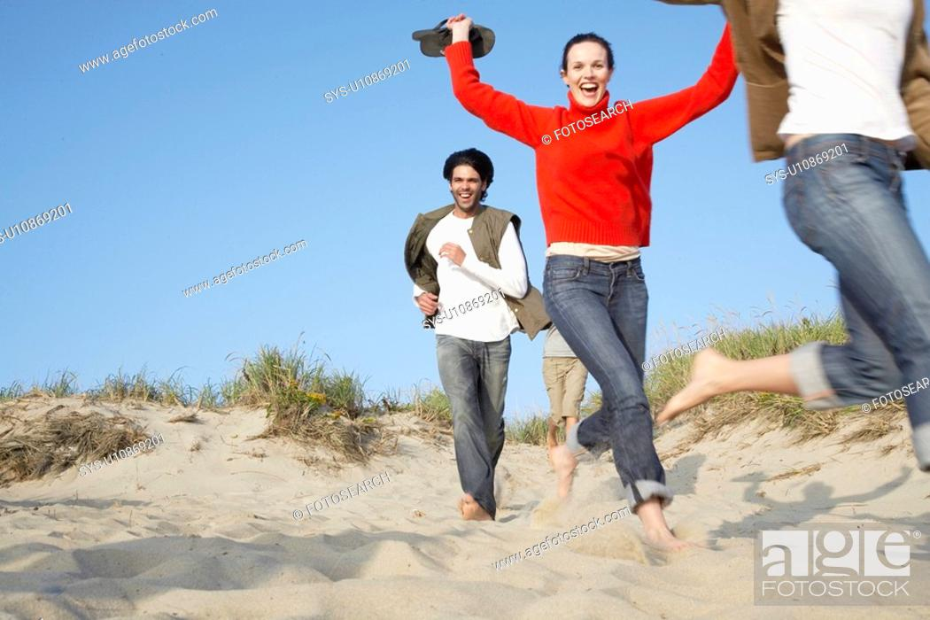 Stock Photo: People running on beach blurred motion, low angle view.