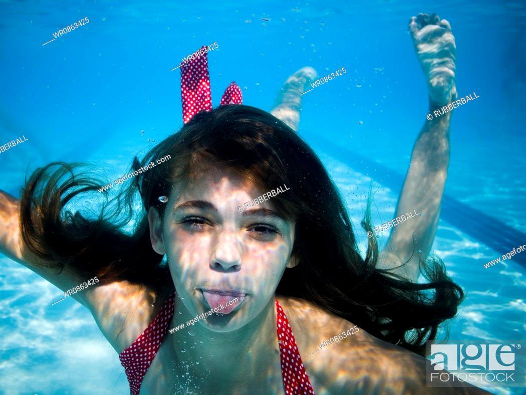 Stock Photo: Girl swimming underwater in pool.