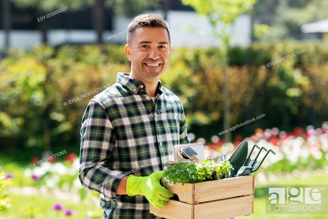 Stock Photo: happy man with tools in box at summer garden.