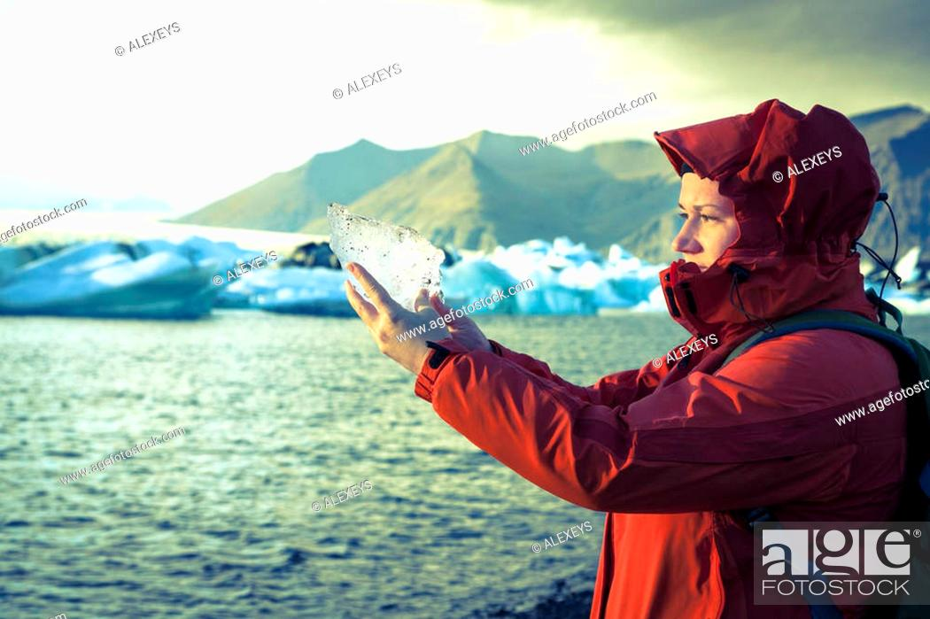 Stock Photo: Woman is holding a piece of ice from the glacier at Jokulsarlon Lagoon in Iceland.