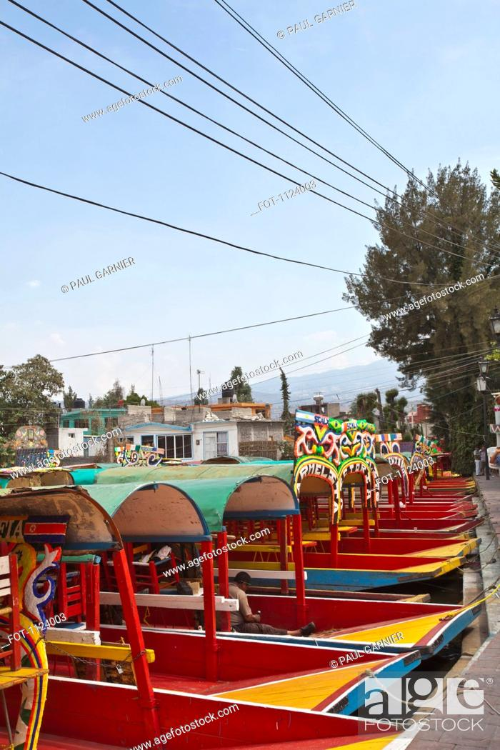 Stock Photo: A row of moored Trajineras, a traditional gondola type Mexican tour boat.