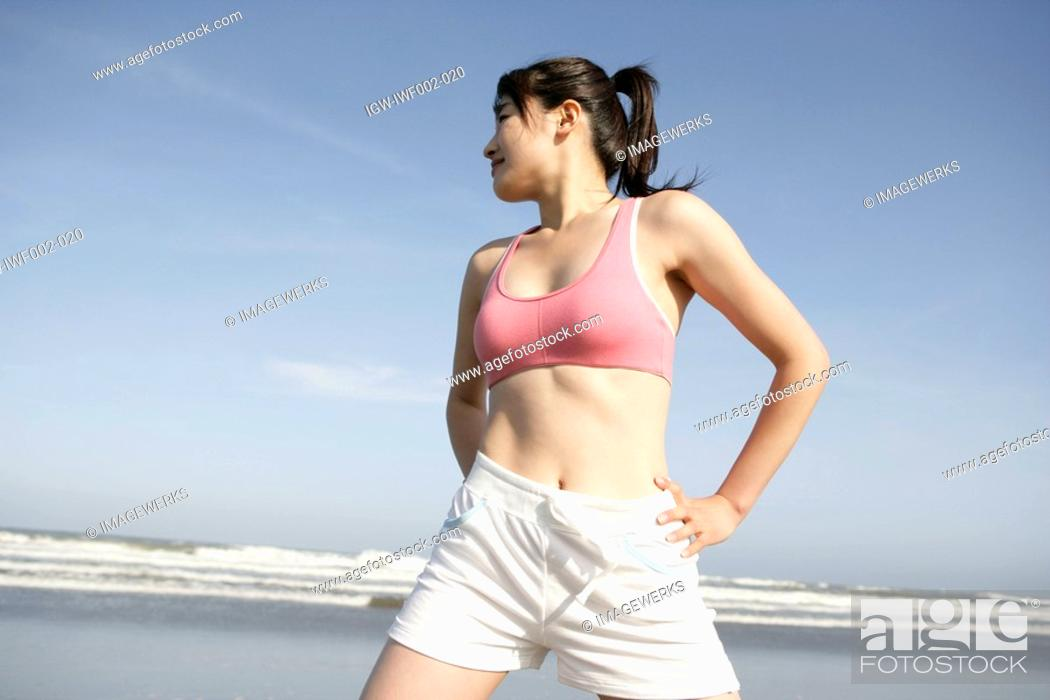 Stock Photo: A young woman exercising on the seashore.