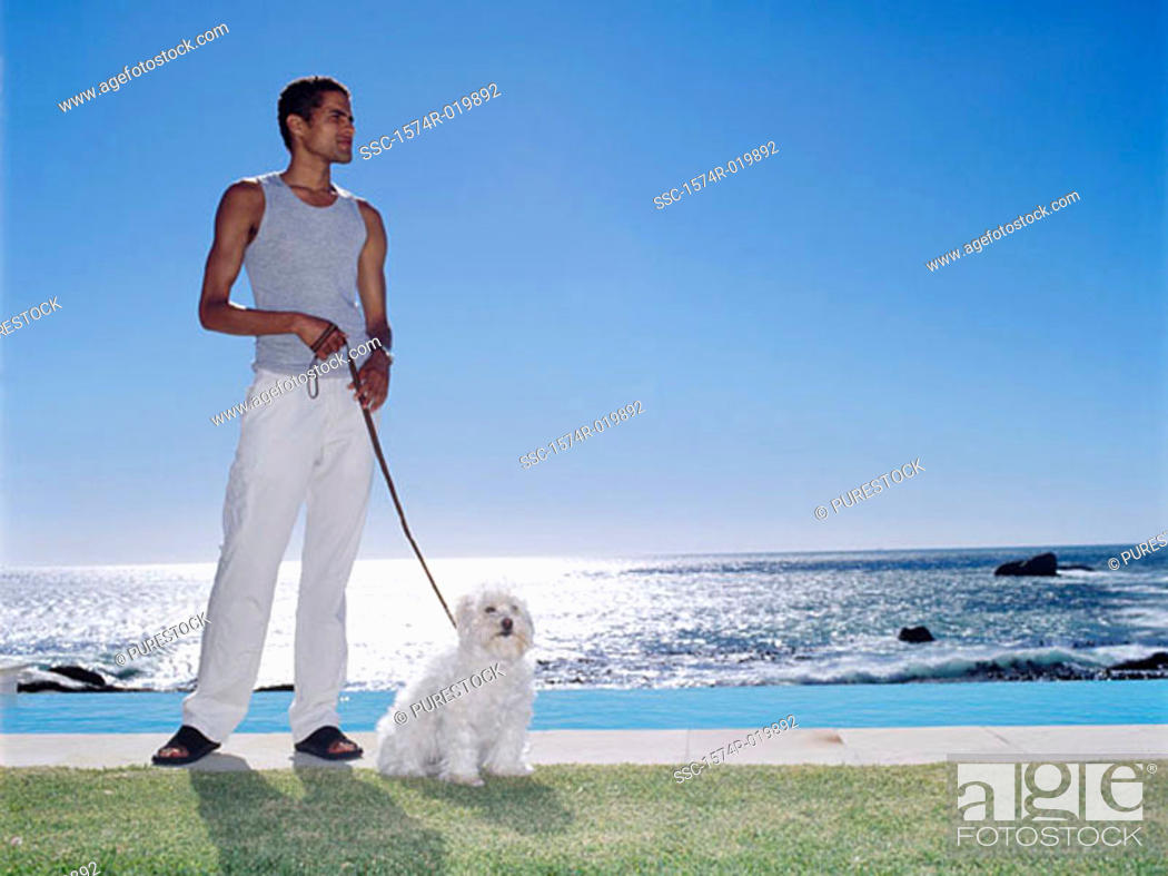Stock Photo: Young man holding a dog on a leash.
