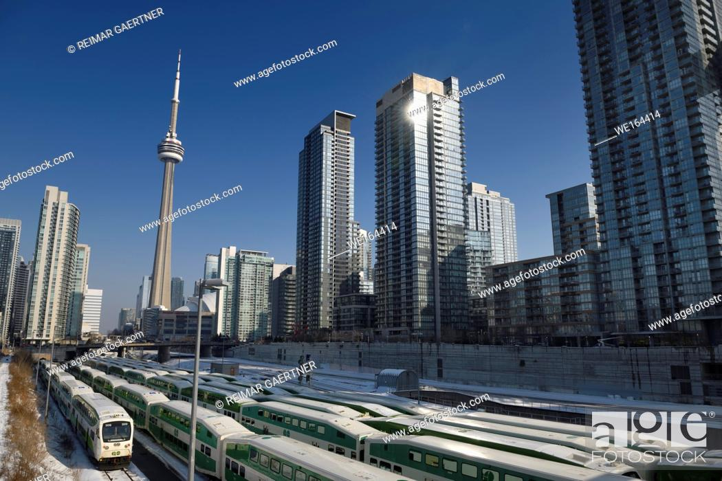 Stock Photo: GO trains on railway tracks in downtown Toronto waiting for rush hour with CN tower and highrise condominium towers in winter.