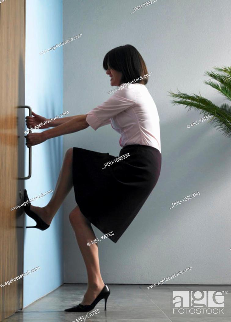 Stock Photo: Businesswoman struggling to open door, foot against wall.