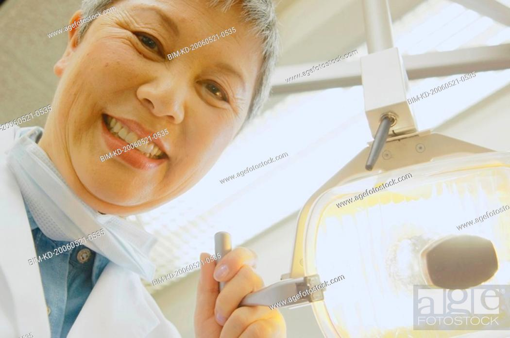 Stock Photo: Senior Asian female dentist adjusting light.