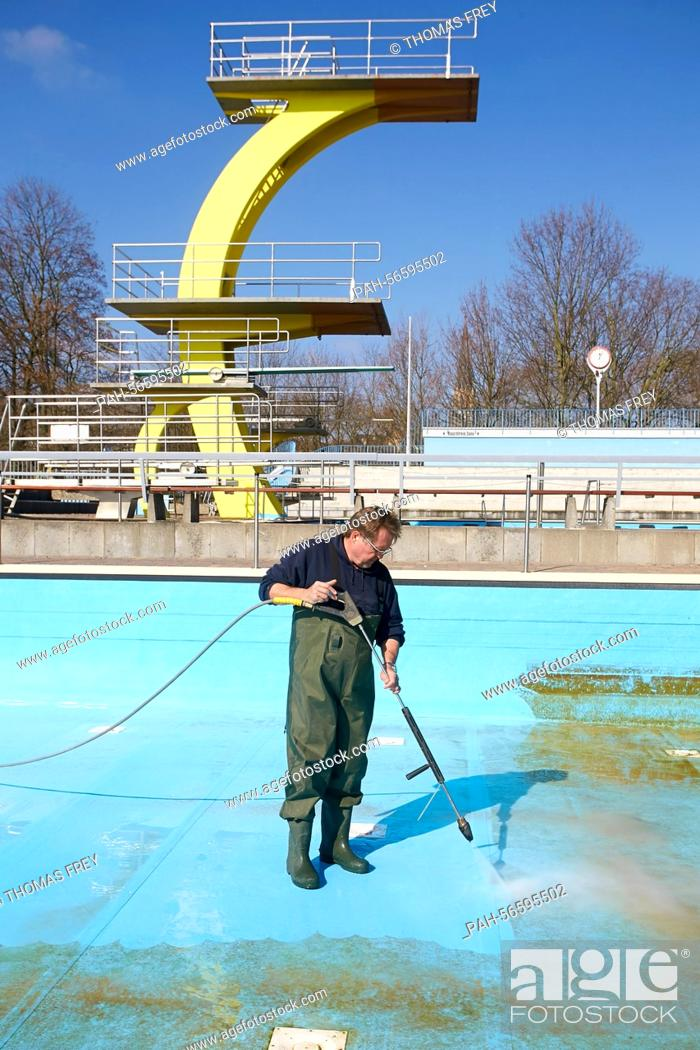 Stock Photo: A staff member cleans the pool of the the public Open air pool in Koblenz, Germany, 11 March 2015. Open air pools are preapring for the forthcoming spring and.