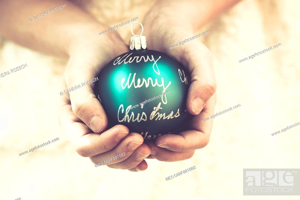Stock Photo: Girl's hands holding green Christmas bauble with the words 'Merry Christmas'.