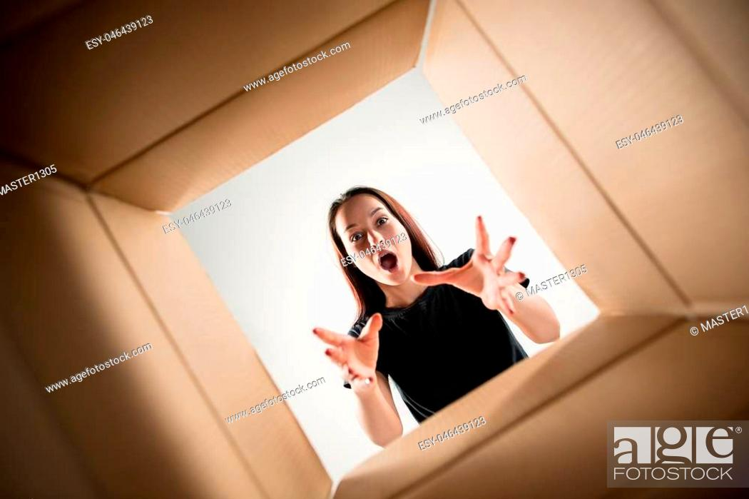Imagen: The surprised woman unpacking, opening carton box and looking inside. The package, delivery, surprise, gift, lifestyle concept.