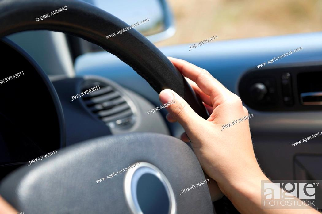 Stock Photo: Close-up of a young woman's hand holding steering wheel.