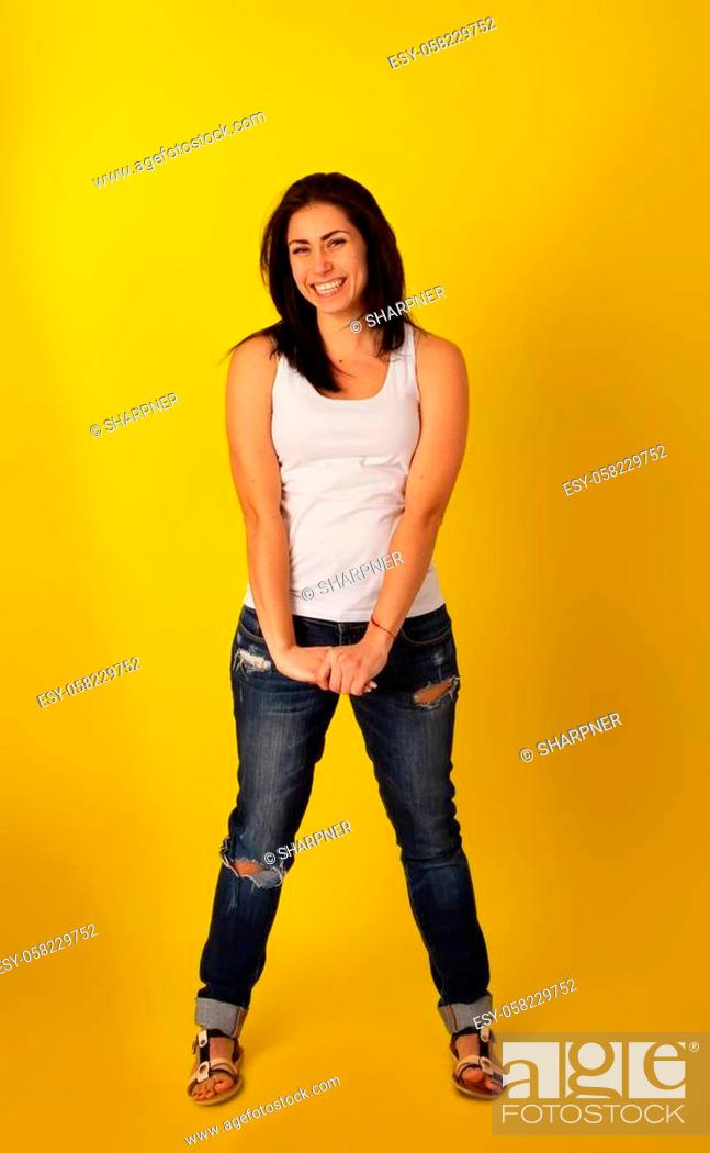 Stock Photo: Pretty girl with dark hair in casual clothes in a good mood is standing on a bright yellow background.