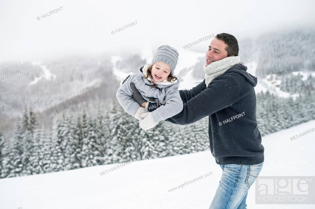 Stock Photo: Father playing with daughter in winter landscape.