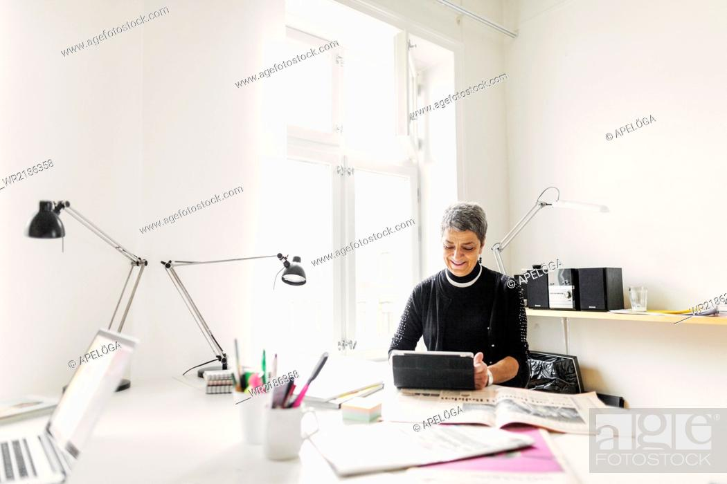 Stock Photo: Businesswoman using digital tablet at desk in office.