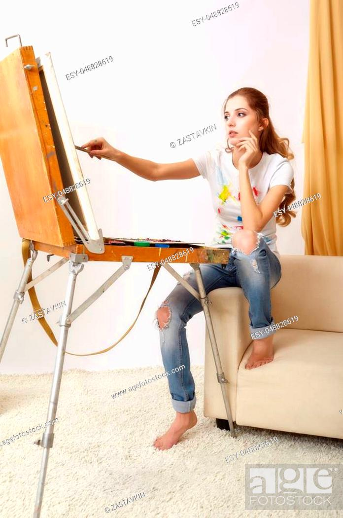 Stock Photo: Painter woman with wooden sketchbook sitting on sofa and painting.