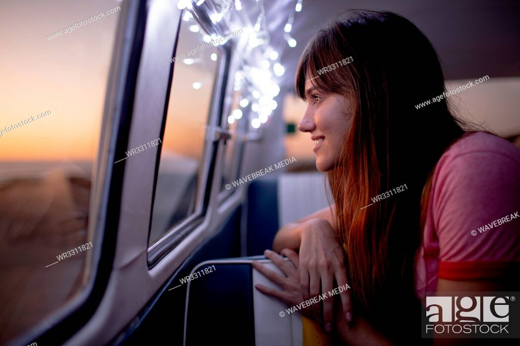 Stock Photo: Woman looking through window of a camper van at beach.