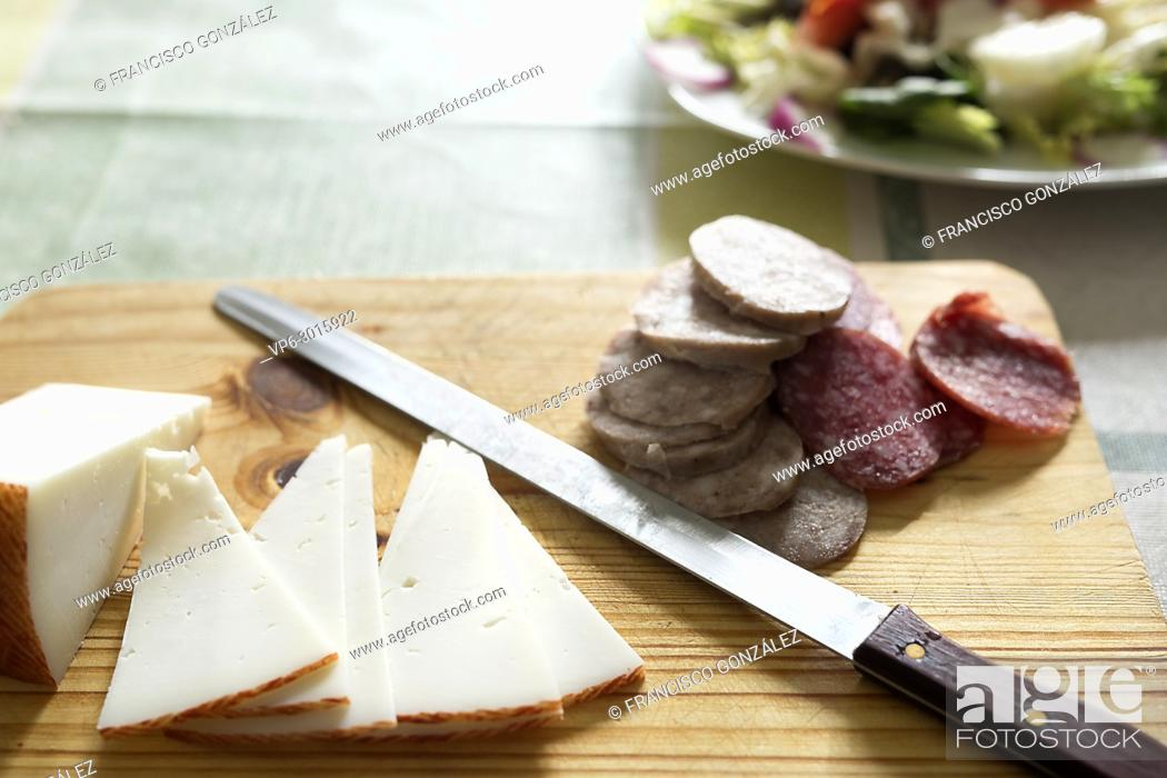 Photo de stock: Cheese and sausages cut on a cutting board. Hoarizontal shot.