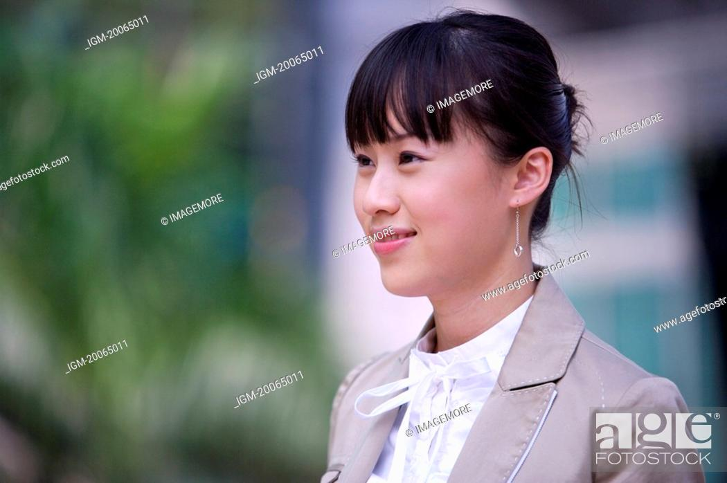 Stock Photo: Young woman looking away with smile.