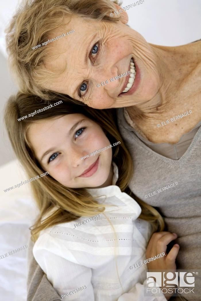 Stock Photo: Senior woman and little girl smiling for the camera, indoors.