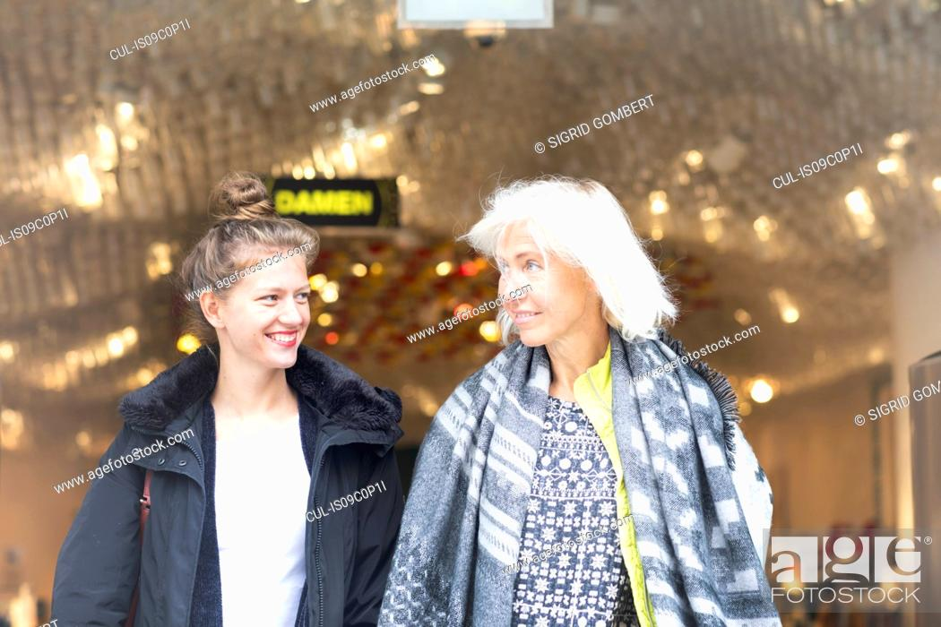 Stock Photo: Mature woman and daughter leaving shop in city.