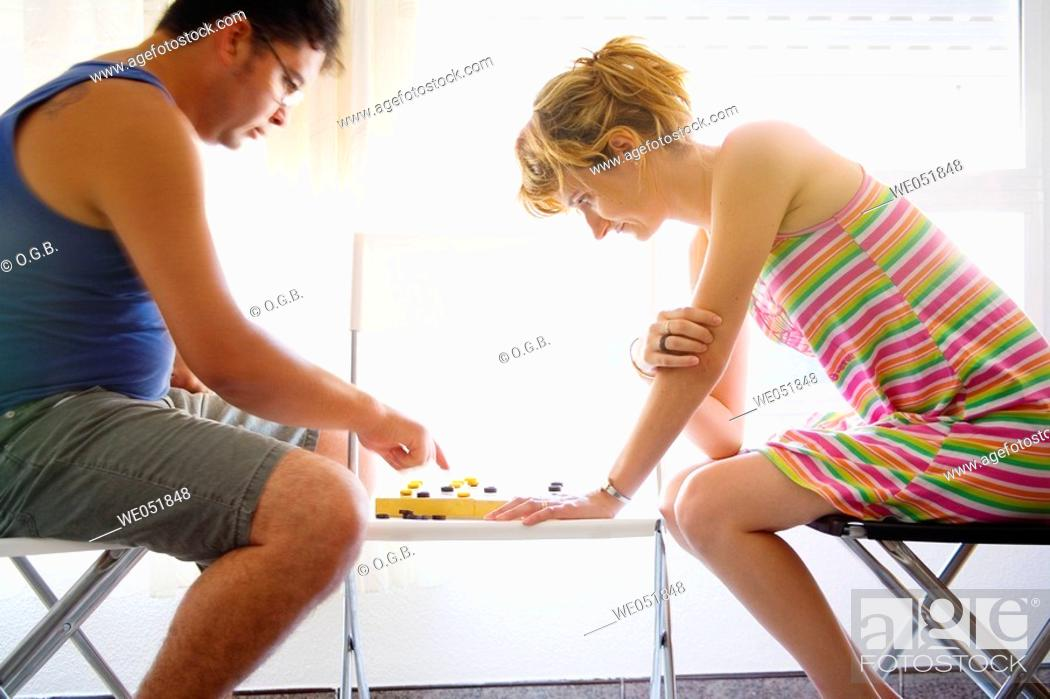 Stock Photo: Couple playing checkers.