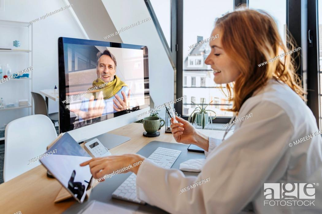 Stock Photo: Smiling patient talking to doctor through computer while sitting at office.