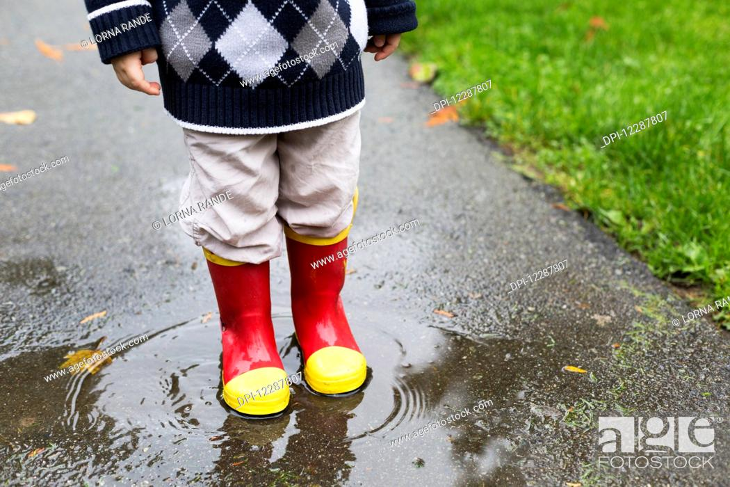 Stock Photo: A young boy with brightly coloured rubber boots standing in a puddle in Bear Creek Park; Surrey, British Columbia, Canada.