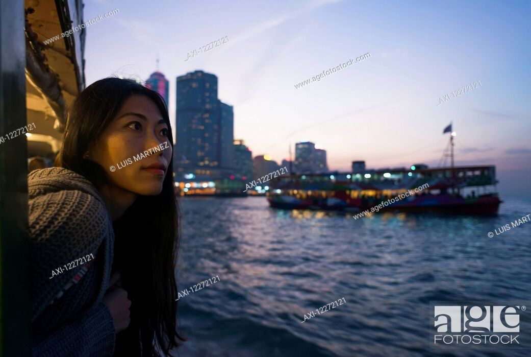 Stock Photo: A young woman at the waterfront at sunset with a a boat and skyline in the background, Kowloon; Hong Kong, China.