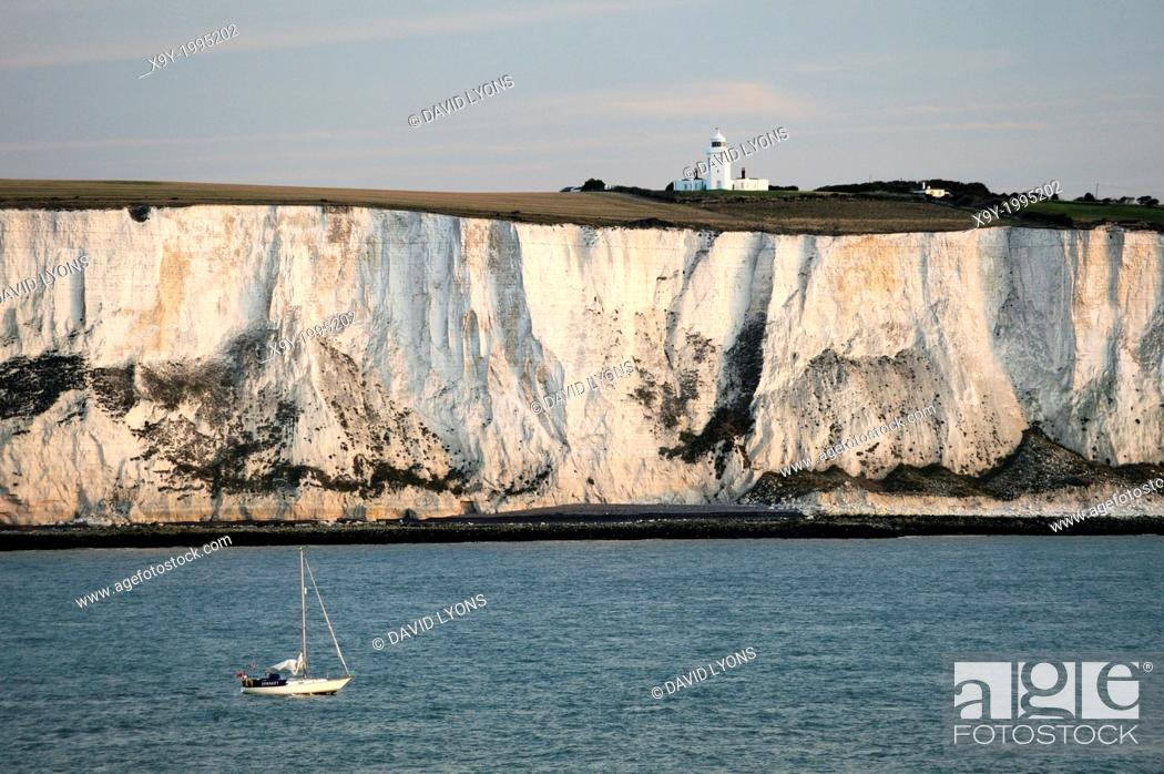 Stock Photo: Yacht passing along the White cliffs of Dover in the English Channel east of Dover below South Foreland lighthouse. Dawn light.