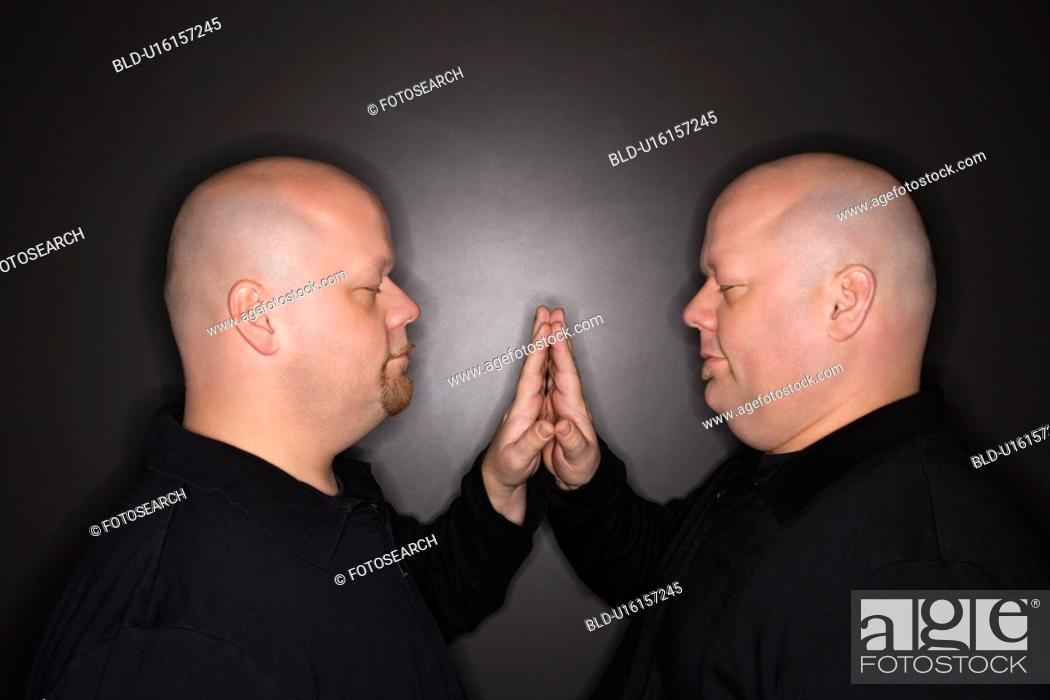 Stock Photo: Bald mid adult identical twin men standing face to face with hands touching.