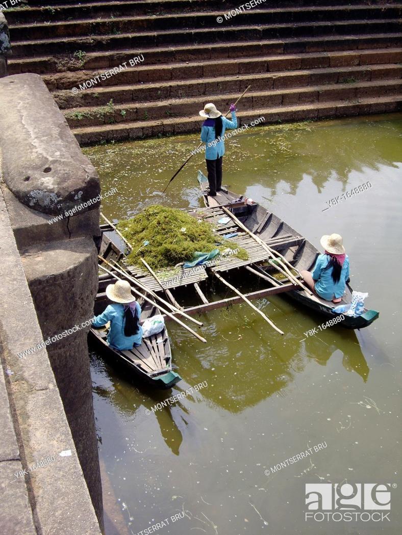 Stock Photo: Three female lake bottom cleaners on boat at Angkor Wat, Cambodia.