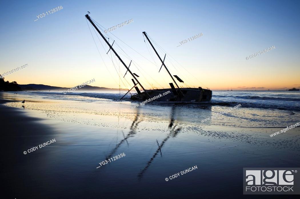 Stock Photo: Santa Barbara, California: Sailboat washed ashore on beach during winter storm.