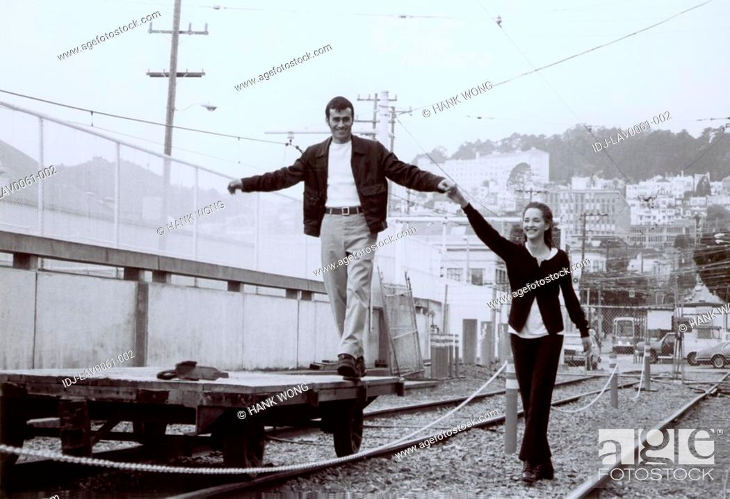 Stock Photo: Young man standing on a trolley and holding hands of a young woman on a railroad track.
