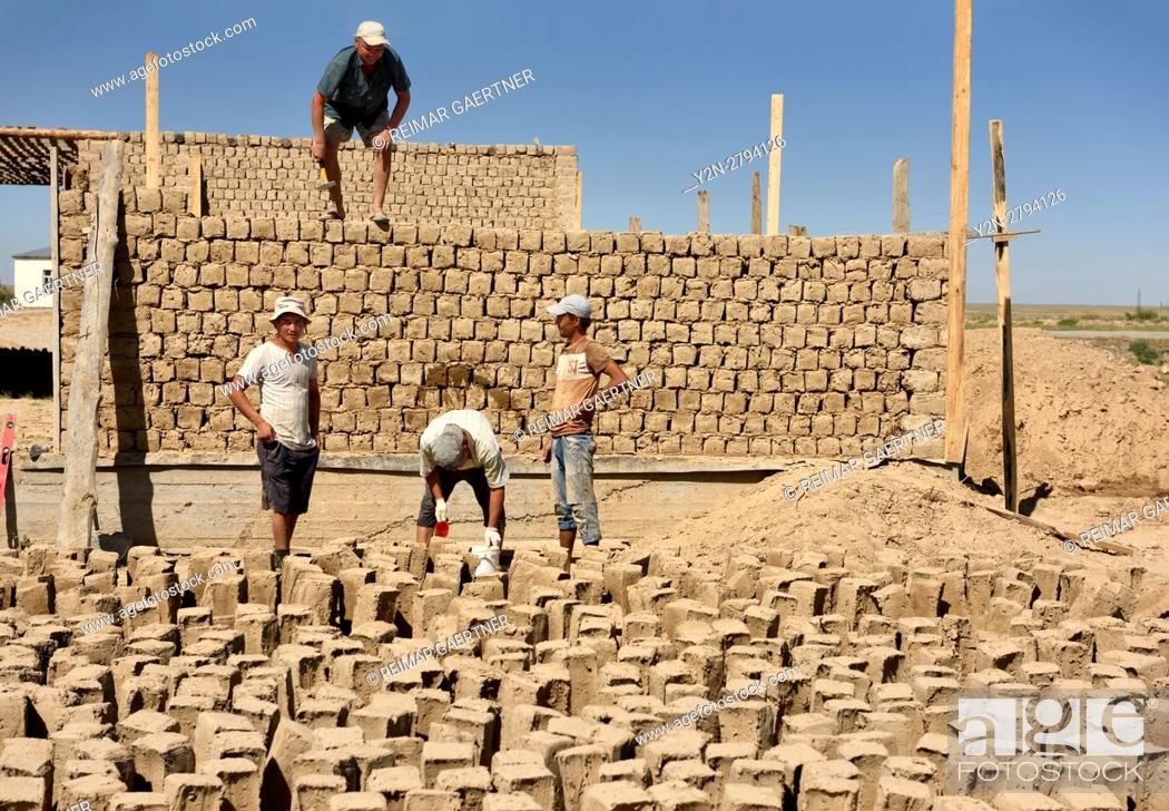 Stock Photo: Construction workers building mudbrick house in development outside Shymkent Kazakhstan.