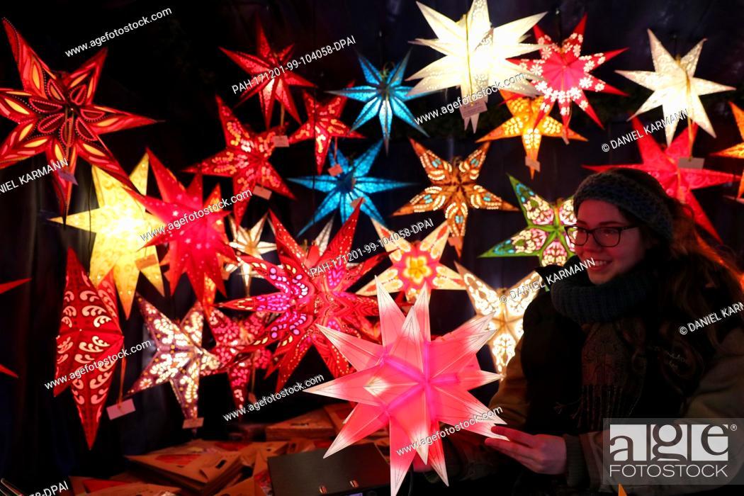 Photo de stock: Christmas stars glow at a stand at the Nuremberg Christmas market in Nuremberg, Germany, 01 December 2017. Photo: Daniel Karmann/dpa.