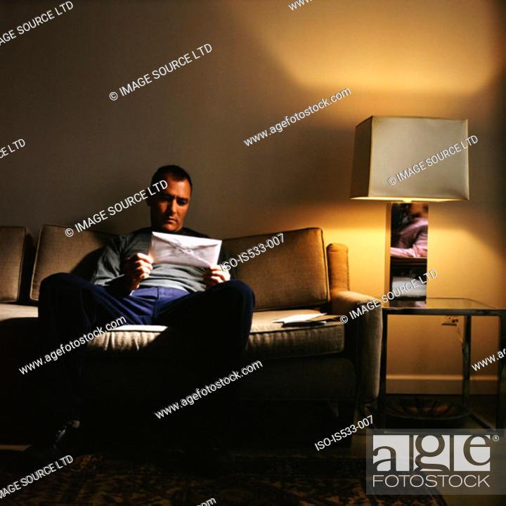 Stock Photo: Man holding envelope on sofa.