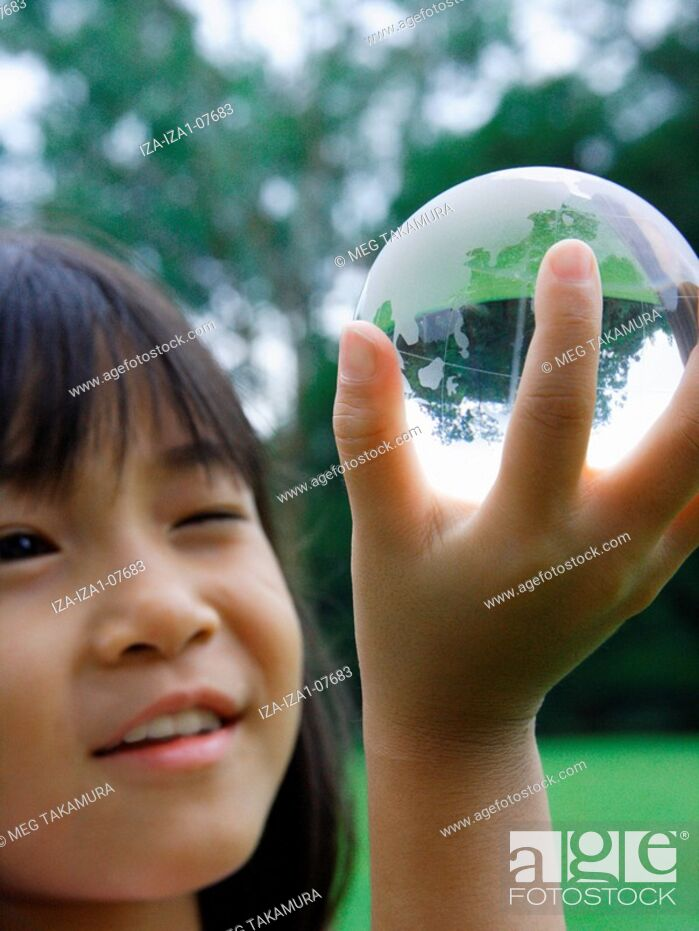 Imagen: Close-up of a girl smiling and holding a globe.