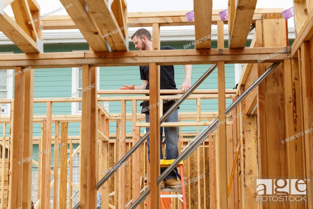 Stock Photo: Caucasian man standing on ladder at construction site.
