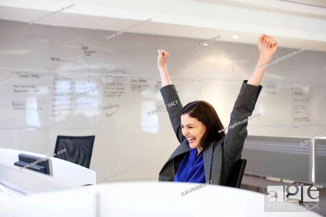 Stock Photo: Enthusiastic businesswoman with arms raised in office.