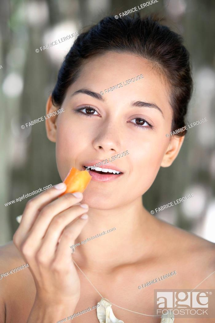 Stock Photo: Portrait of a young woman eating a carrot.