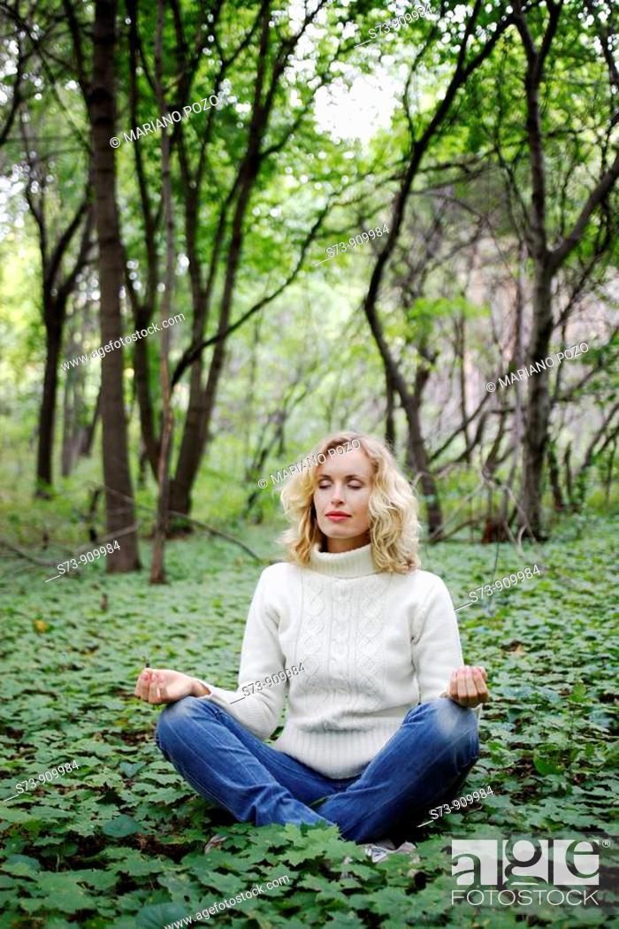 Stock Photo: Young woman doing yoga in a russian forest, Molodeskiy Kurgan National Park, Samara Region, Russian Federation.
