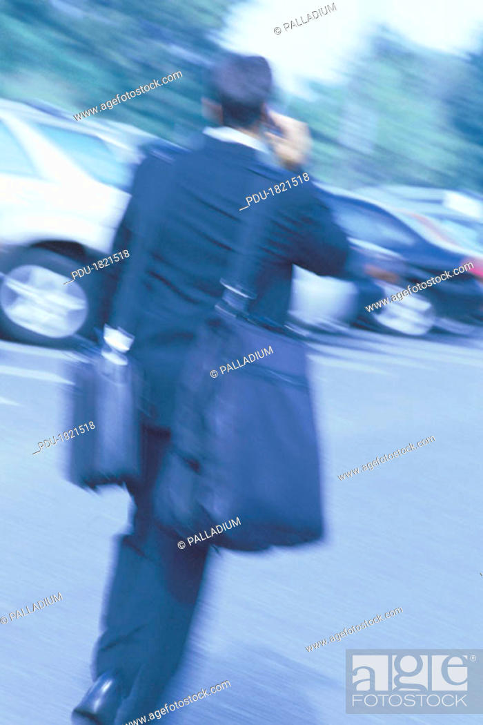 Stock Photo: Man walking with luggage and talking on cellphone, motion blur.