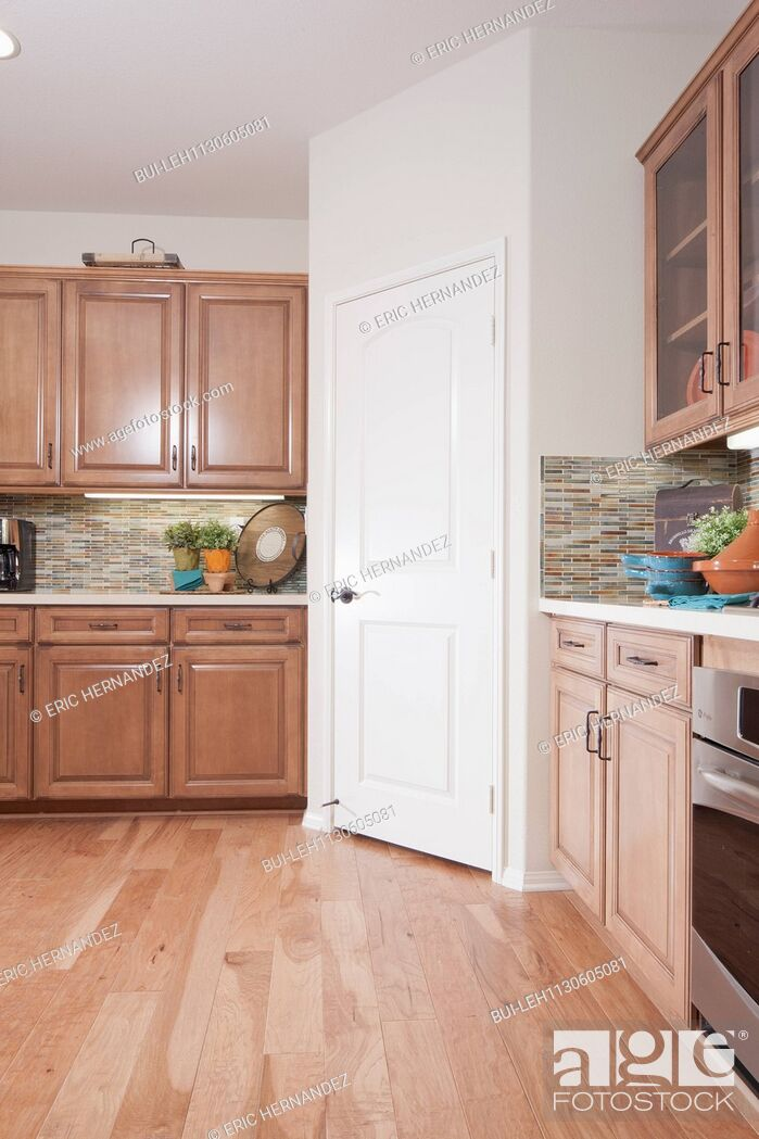Imagen: Wooden cabinets and closed door in kitchen.