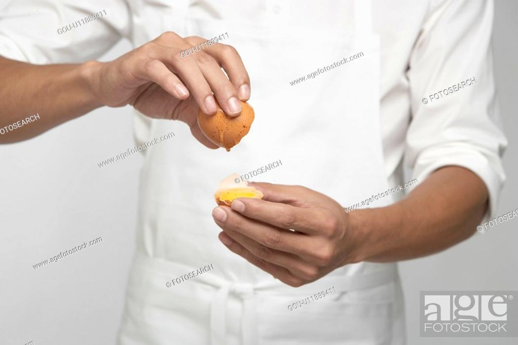 Stock Photo: Chef cracking brown egg (mid section).