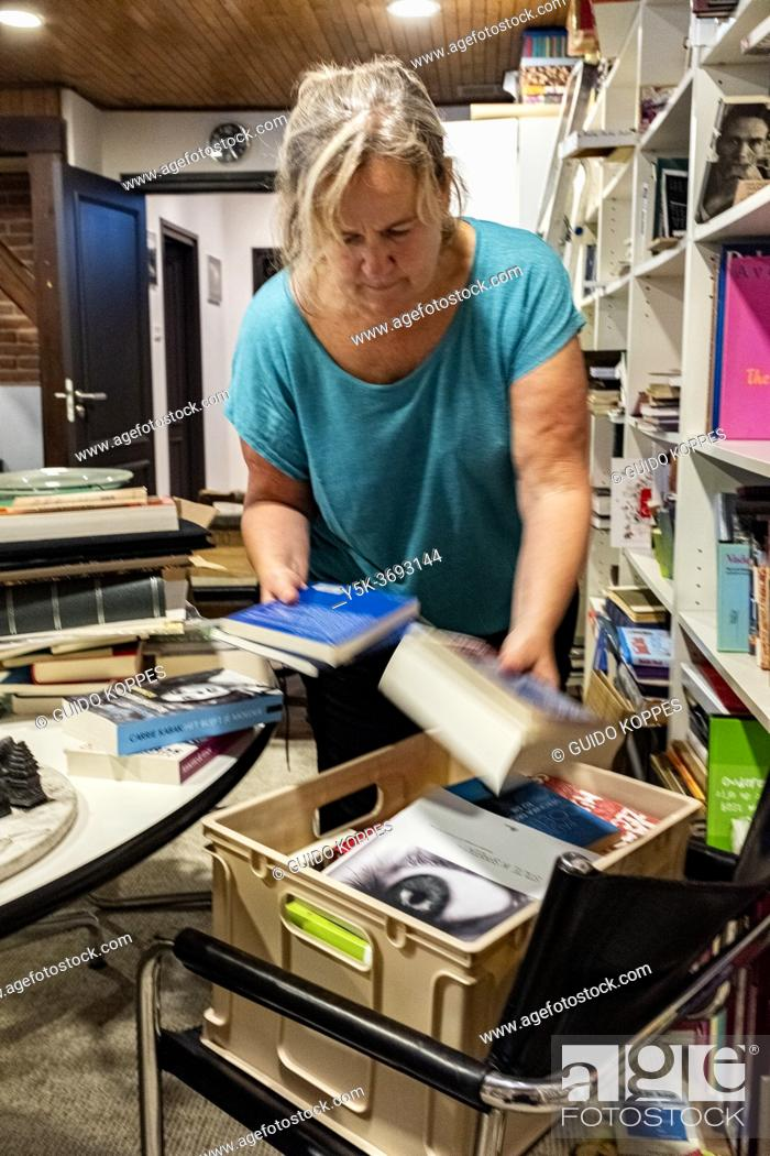 Stock Photo: Oisterwijk, Netherlands. Elder woman cleaning up the basement room of her rural country villa after collecting years and years of books.
