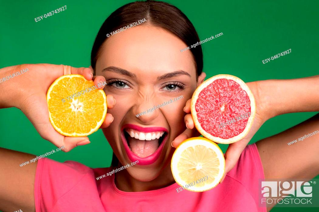 Stock Photo: Portrait of delighted female person with rose lipstick showing delicious fruits in her hands. Isolated on background.