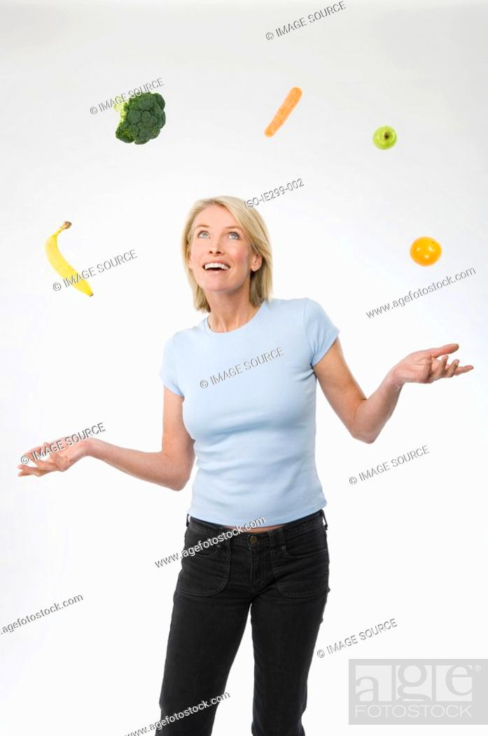 Stock Photo: A woman juggling fruit and vegetables.