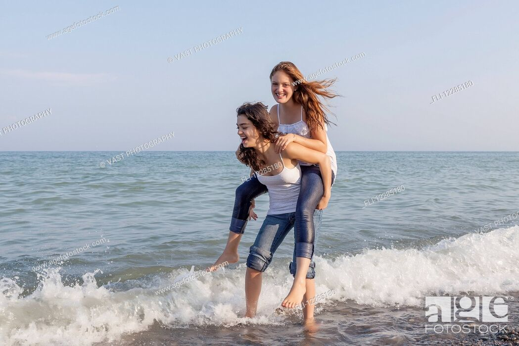 Stock Photo: Two girls playing piggyback at beach; Toronto, Ontario, Canada.