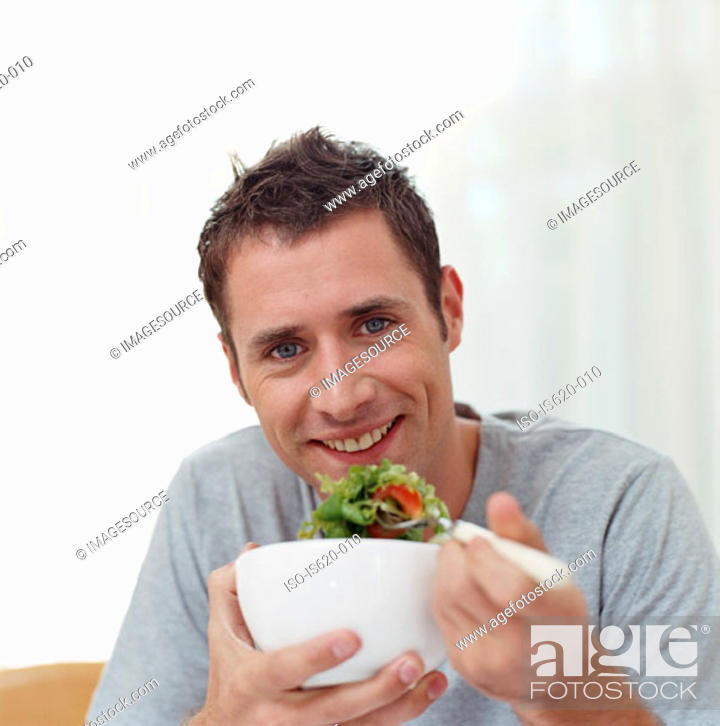 Stock Photo: Man eating a bowl of salad.